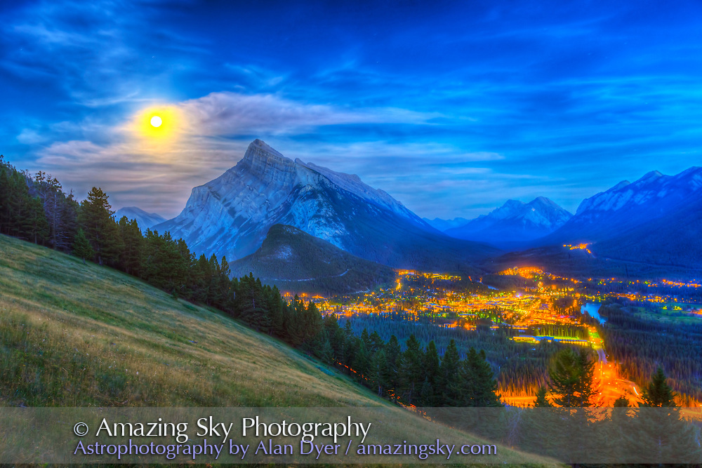 The supermoon of August 10, 2014 rising behind Mt. Rundle and Banff townsite, as shot from the Mt. Norquay viewpoint looking south over the valley. This is an HDR high dynamic range stack of 8 exposures to capture the great range in brightness from the sky around the Moon (the Moon itself is inevitably overexposed) to the dark ground and trees. I've turned up the HDR intensity a bit more than natural to bring out cloud structure but that does give the image an HDR look. I shot this at the end of a 700-frame time-lapse, with the 16-35mm lens and Canon 6D. HDR processed with Photomatix Pro.