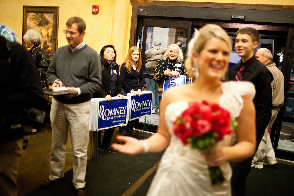 New bride Ali Banwart makes her way through the lobby of the Stoney Creek Inn on the way to her wedding reception as Republican presidential candidate Mitt Romney meets with voters on Saturday, December 31, 2011 in Sioux City, IA.