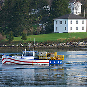 Patriotically painted lobster boat heading out to sea near Bristol Maine