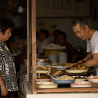 Vendors at an 80 year old porridge shop on Pantai Street