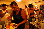 Several family members from Chicago visiting Lula Walker eat at her restaurant Lula's Kitchen on Sapelo Island, Georgia. Mrs. Walker is one of several African  Geechee-Gullah residents facing a property tax increase close to 1,000 percents from 2011 county tax assessments. Walker can trace her family's heritage back to slavery before the Civil War. (Stephen Morton for The New York Times)