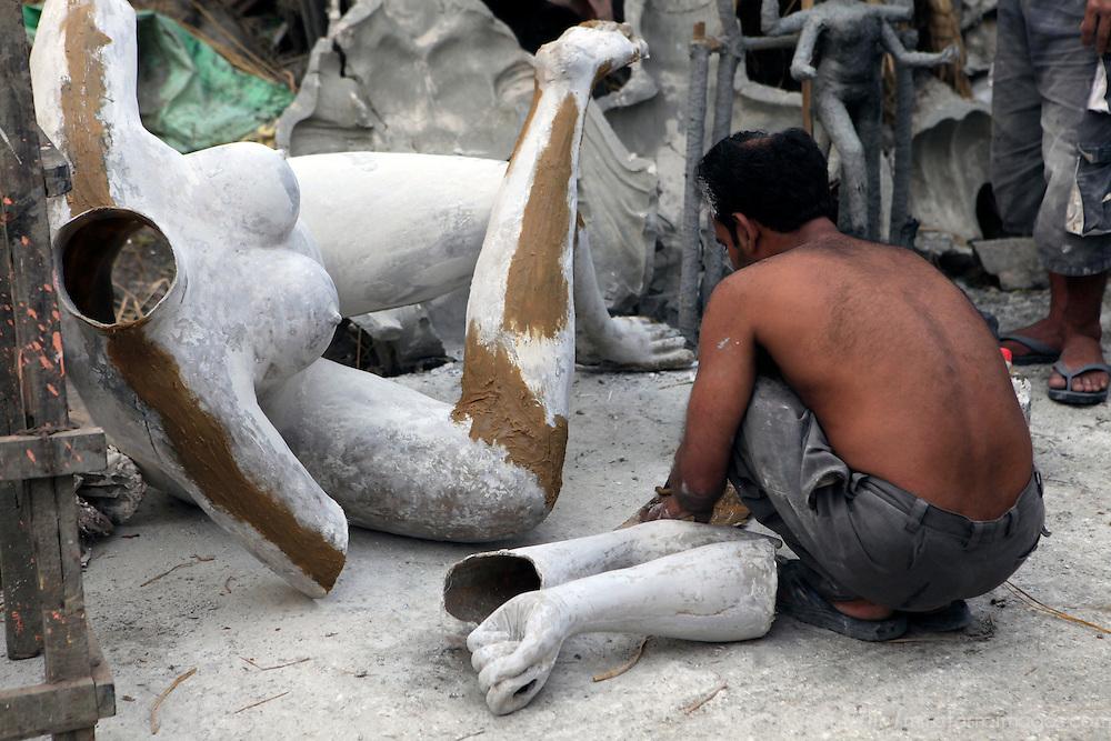 Asia, India, Calcutta. Sculptor works on limbs at the potter's village of Kumartuli in Calcutta.