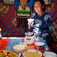 Inside a fancy yurt a Mongolian woman offers guests milk tea (Nai Cha) and a sweet yogurt dip with toasted millet and sugar (Uremtei Khool). in the background hangs a portrait of Genghis Khan, Inner Mongolia, China.
