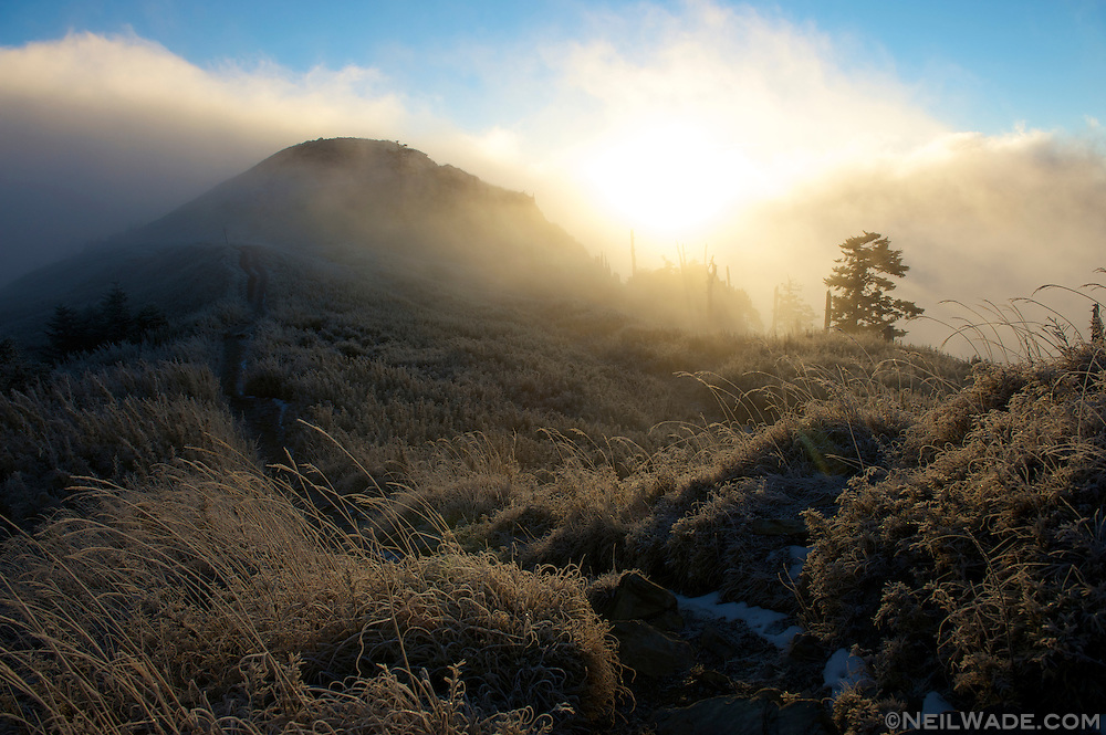 The East Peak of Snow Mountain pokes out of the mist during an early morning sunrise.