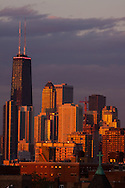 The John Hancock Building rises above the northern portion of the Chicago skyline as the last rays of sun on a warm summer evening reflect off the glass and steel of the buildings. A summer storm has just passed over and has moved out into Lake Michigan.
