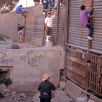 Undocumented migrants gather along the U.S.-Mexico border in San Diego, California. Please contact Todd Bigelow directly with your licensing requests. PLEASE CONTACT TODD BIGELOW DIRECTLY WITH YOUR LICENSING REQUEST. THANK YOU!