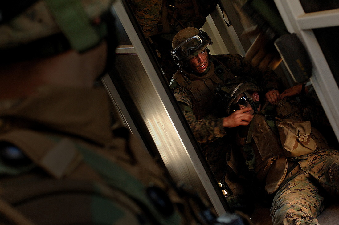 """A U.S. Marine, attached to the 3rd Marine Expeditionary Brigade, tends to the needs of an """"injured"""" unit member, while his team continues to advance building-to-building, clearing each structure. — © Tsgt Jeremy Lock/"""