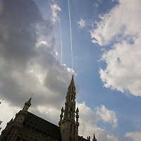 Trip to Amsterdam on vacation.  Contrails paint lines behind the spire of the main bell tower in the main square.  Grand place plaza.