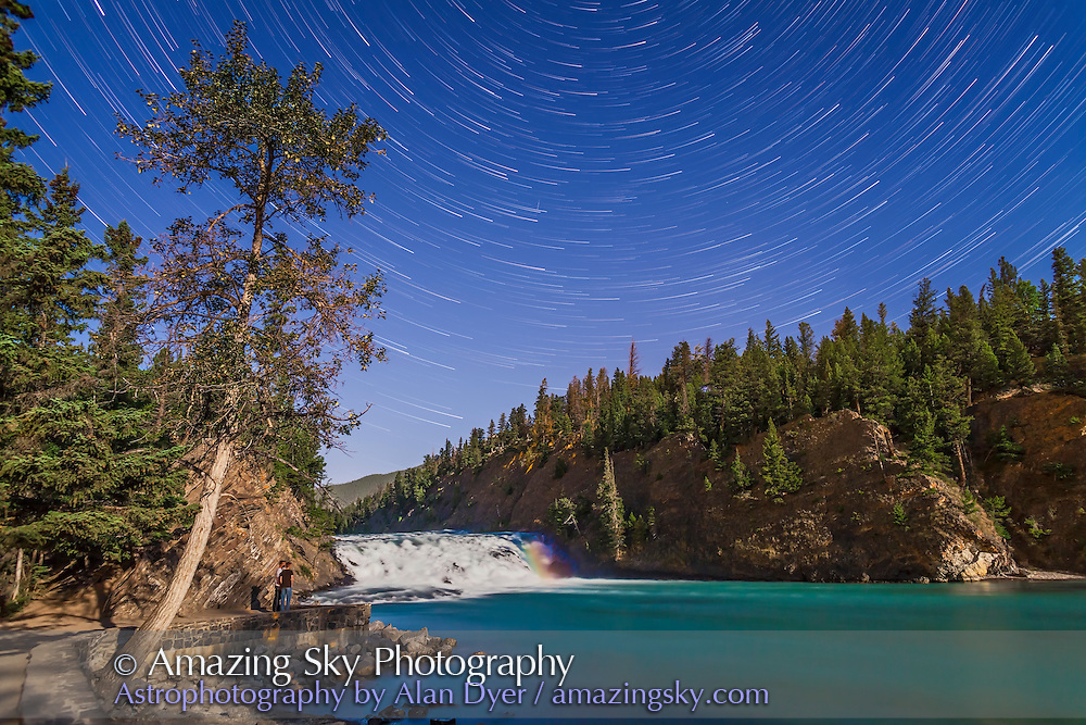The stars of the northern sky circling in star trails over Bow Falls, on the Bow River, Banff, Alberta. This is a stack of 80 images, each 30 seconds at f/4 and ISO 800 with the 24mm lens and Canon 5D MkII. Stacked with Advanced Stacker Plus actions using Long Streak effect. The foreground is from one exposure. and includes a faint moonbow at right over the falls as well as two people who wandered in for a look and stood still long enough for a single exposure.