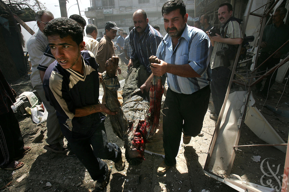 The body of a victim is rushed from the scene of a suicide car bombing in Tahrir square in Baghdad May 07, 2005. The bombing, which targeted a passing civilian contractor convoy, killed at least 6 persons and wounded another 30 during the late morning explosion in the busy commercial area in central Baghdad.