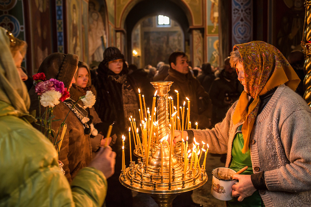 KIEV, UKRAINE - JANUARY 26: Women light candles inside Mikhailovsky Cathedral before a memorial service for Mikhail Zhiznevsky, 25, an anti-government protester who was killed in clashes with police, on January 26, 2014 in Kiev, Ukraine. After two months of primarily peaceful anti-government protests in the city center, new laws meant to end the protest movement have sparked violent clashes in recent days. (Photo by Brendan Hoffman/Getty Images)