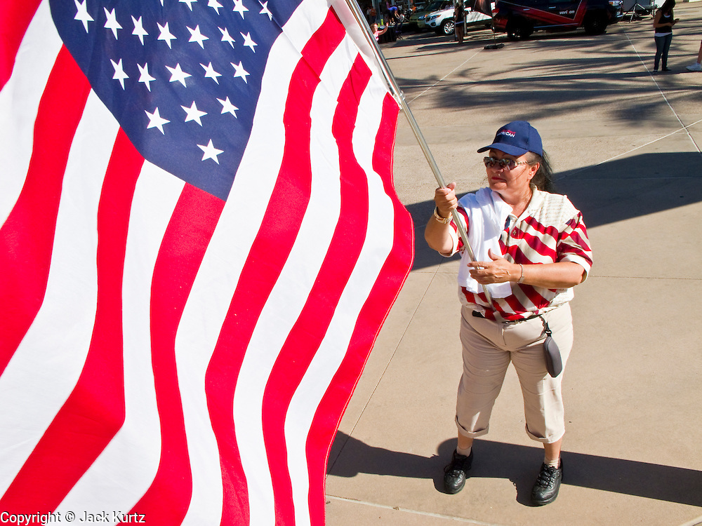 """25 MAY 2010 - PHOENIX, AZ: A woman carries an American flag in front of US Airways Arena in Phoenix, May 25. People opposed to illegal immigration and in favor of Arizona SB1070 picket the Phoenix Suns playoff game against the Los Angeles Lakers Tuesday. About 10 people attended the protest. One person opposed to SB1070 held a counter demonstration. SB1070 makes it an Arizona state crime to be in the US illegally and requires that immigrants carry papers with them at all times and present to law enforcement when asked to. People are picketing the Suns games because Suns owner Robert Sarver has expressed opposition to the law and has had the Suns wearing jerseys that say """"Los Suns.""""  PHOTO BY JACK KURTZ"""