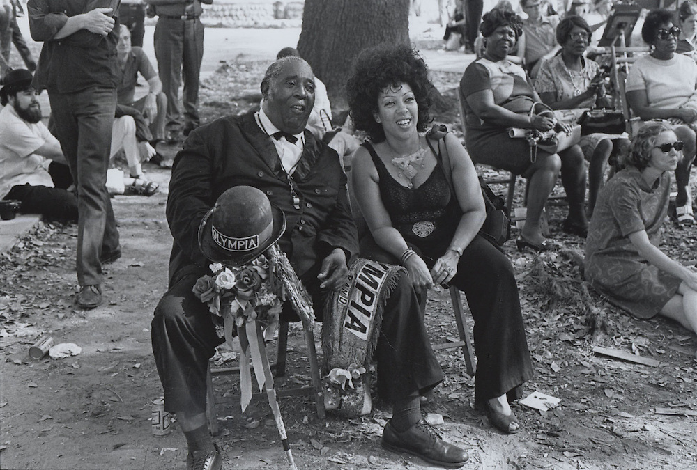 Olympia Brass Band leader sits on bench and listens to music during the third Louisiana Jazz and Heritage Festival at the New Orleans Fairgrounds in 1972.