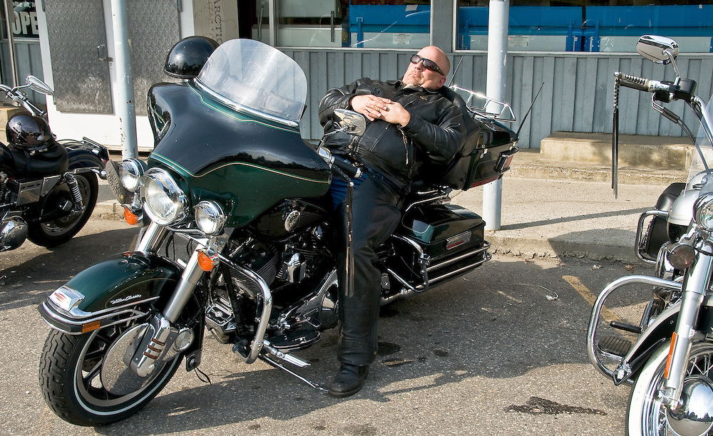 A biker rests (or sleeps) near a local supermarket in New Denver, Canada.