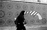 An Iranian women in headscarf walking in front of the wall of the former US embassy, known as the US Den of Espionage. The wall, filled with anti-American drawings and paintings. Tehran, Iran, 2007