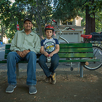 "Miguel Castro with his ight year old son, Miquel on a bench near Calistoga Elementary School.  ""We ride bicycles every night...tonight we rode out to the Guyser to see where the fire was.""  707-942-0497"