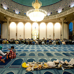 London, UK - 21 July 2012: Two children sit near a banquet while Muslim faithful pray for the breaking of the fast at the London Central Mosque in Regent's Park