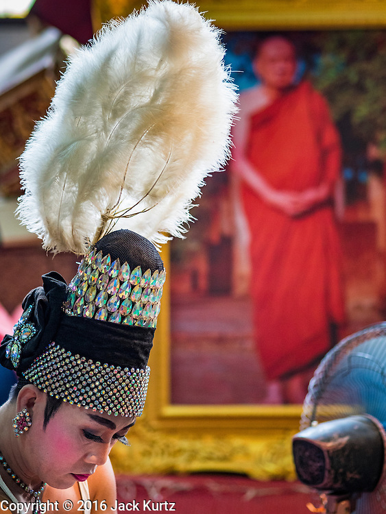 "30 JANUARY 2016 - NONTHABURI, NONTHABURI, THAILAND: A performer gets ready for a ""likay"" show at Wat Bua Khwan in Nonthaburi, north of Bangkok. The troupe used a storage room at the temple as a dressing room. Likay is a form of popular folk theatre that includes exposition, singing and dancing in Thailand. It uses a combination of extravagant costumes and minimally equipped stages. Intentionally vague storylines means performances rely on actors' skills of improvisation. Like better the known Chinese Opera, which it resembles, Likay is performed mostly at temple fairs and privately sponsored events, especially in rural areas. Likay operas are televised and there is a market for bootleg likay videos and live performance of likay is becoming more rare.     PHOTO BY JACK KURTZ"