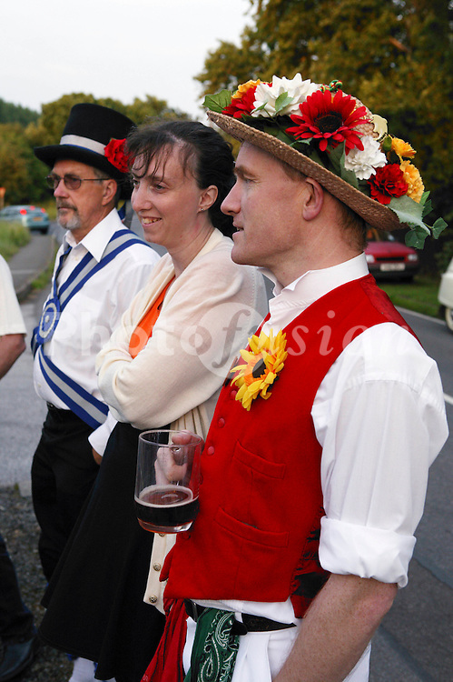 Morris dancers wearing costumes standing outdoors talking,
