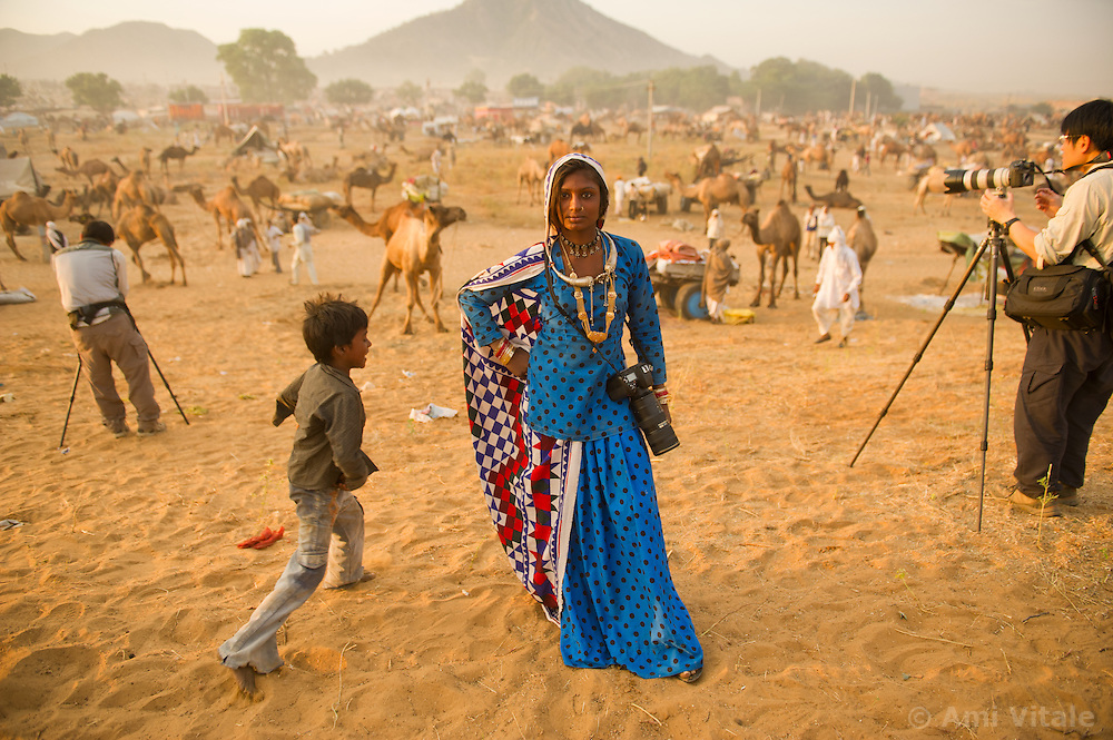 Subita Devi, 13 poses with a professional camera as other tourists take photos at the world's largest annual cattle fair in the desert town of Pushkar, in the Indian state of Rajasthan. Every year thousands of camel herders from the semi-nomadic Rabari tribe, who make a living rearing animals, travel for two to three weeks across 500 kilometers to set up camp in the desert dunes near Pushkar to sell their livestock. The herders sell more than 20,000 camels, horses and other animals at the annual cattle fair.