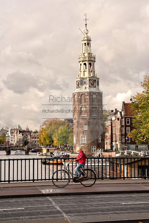 Bicyclist crossing Prins Hendrikkade at the Montelbaanstoren Tower in Amsterdam.