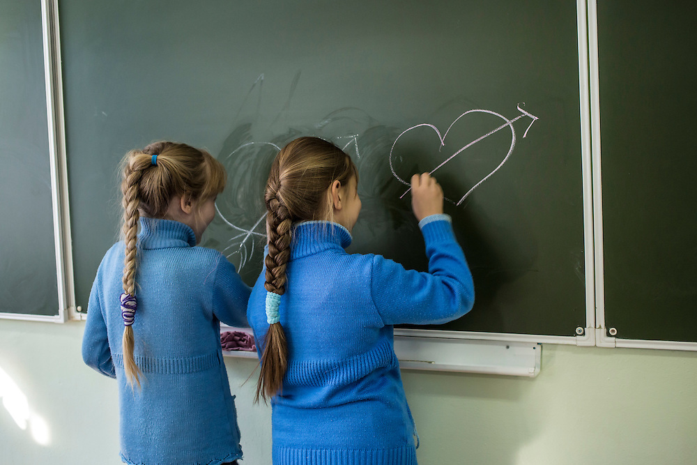 Girls play at the chalk board during a sewing class at a local school on Sunday, October 20, 2013 in Baikalsk, Russia.