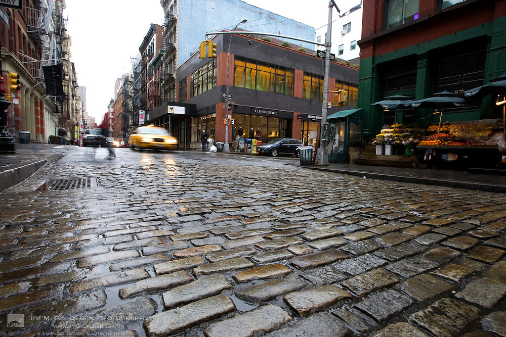 A pedestrian crosses Greene Street while a taxi cab passes by in New York City's SoHo district in the rain