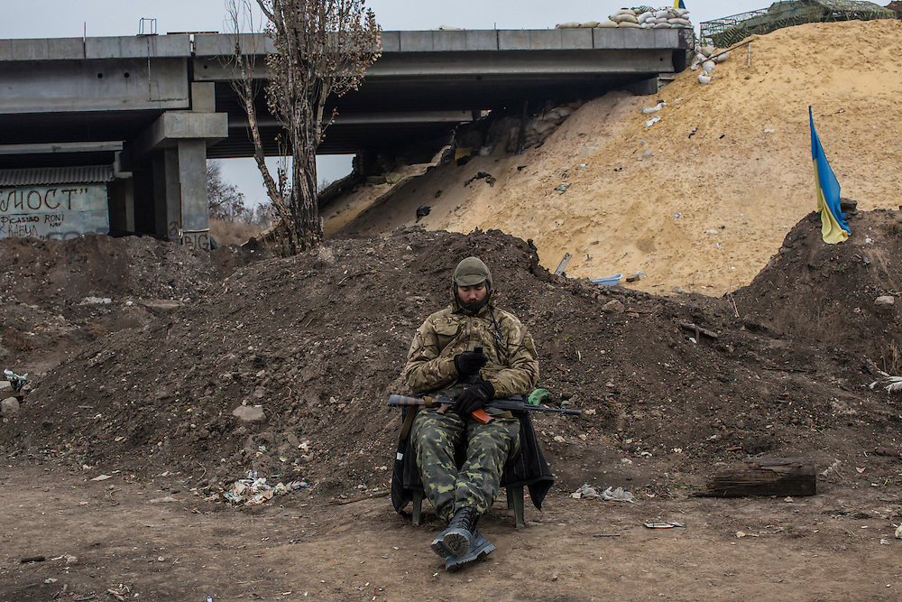 PERVOMAISKE, UKRAINE - NOVEMBER 18, 2014: Grigoriy Matyash, a member of the 5th platoon of the Dnipro-1 brigade, a pro-Ukraine militia, guards their post underneath a bridge in Pervomaiske, Ukraine. CREDIT: Brendan Hoffman for The New York Times