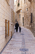 A father walks with his young child on a narrow street in the Jewish Quarter of the Old City of Jerusalem. WATERMARKS WILL NOT APPEAR ON PRINTS OR LICENSED IMAGES.