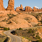 The La Sal Mountains rise behind arches, buttes, and pinnacles of the Windows Section of Arches National Park, Utah, USA. The park road curves through fascinating sandstone scenes.