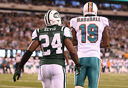 October 17, 2011; East Rutherford, NJ, USA; New York Jets cornerback Darrelle Revis (24) talks to Miami Dolphins wide receiver Brandon Marshall (19) after breaking up a pass during the first half at the New Meadowlands Stadium.