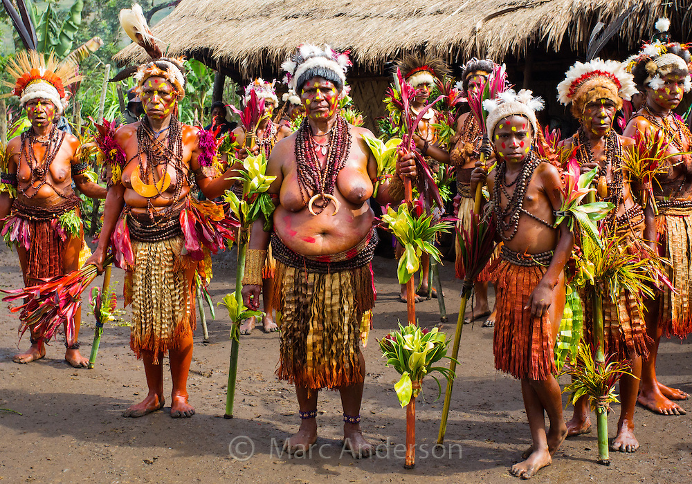 Matriach of the Selehoto Alunumuno tribe standing in a group. Her face is painted and she is wearing traditional dress made from animal fur, flowers, feathers, beads and leaves. Photo taken by a small village in the Papua New Guinea highlands.
