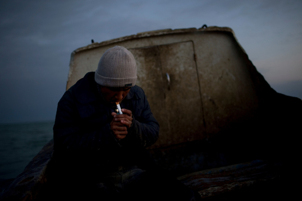 CREDIT: DOMINIC BRACCO II..SLUG:PRJ/KAZAKHSTAN..DATE:11/1/2009..CAPTION:Gaziz Yeleusizov, 22 of Aralsk, lights two cigarettes while fishing on the Aral Sea on November 1, 2009.  ..Aral Sea Overview: ..During the 1960s the USSR began irrigating the waters of the Aral Sea in southern Kazakhstan to combat their growing food crisis. The Soviets severely miscalculated and water began receding quickly from the port cities. The waters continued to recede. By 2000 the water was 80 km away from the city of Aralsk, a main seaport in Kazakhstan. In 2005 with help from the World Bank, construction began on a 13km dike that locals hoped would bring the waters back to their original shores. The project raised water quality and fishing was able to resume, however four years after completion of the dike the water is still 50km from Aralsk's port. Locals seem mixed on the possibility of the sea returning after more than 40 years without the sea. Fishermen from Aralsk make a three-hour path through soft desert road along the former seabed. The only source of income for many is cattle, horses, and camels, which have, began to overgraze the areas of the former seabed and surrounding desert. Because of this nutrient rich topsoil is lifted by the wind and the process of desertification continues.  .