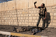 Iraq, Mosul: An Iraqi army soldier takes a selfie with the dead body of an ISIS fighter. Alessio Romenzi