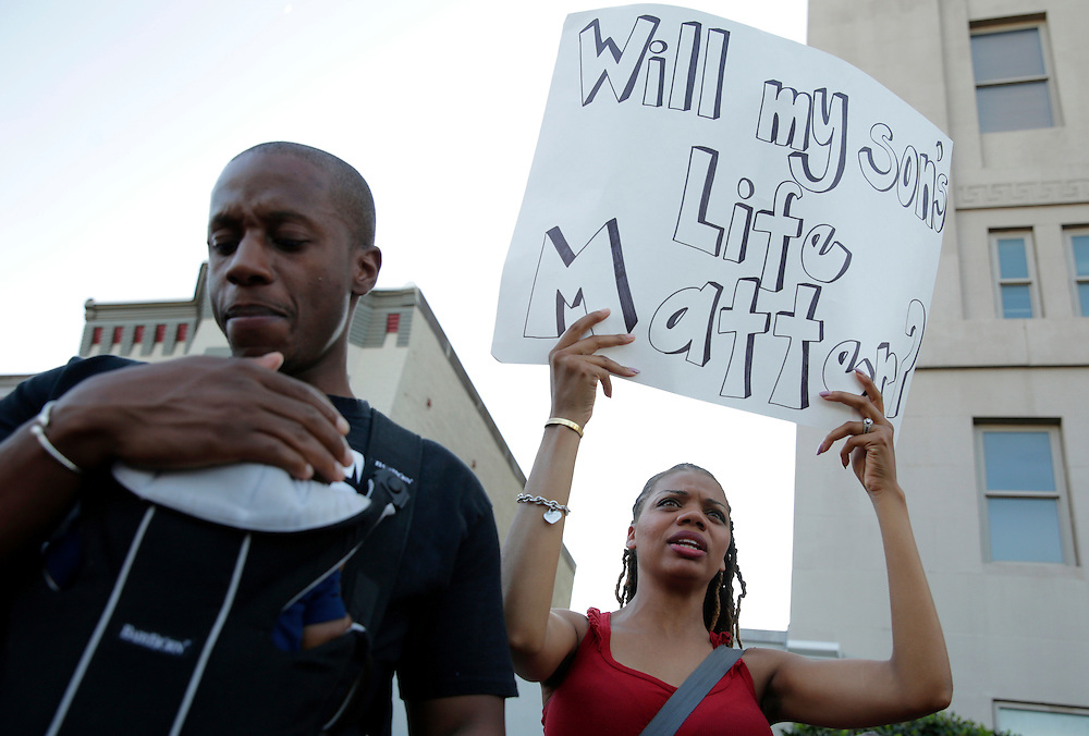 Alex Brown carries his two-month-old son Noah as his wife Lakeisha carries a sign during a Black Lives Matter protest in Washington, U.S., July 9, 2016.      REUTERS/Joshua Roberts