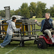 """Freshman Gustavo Vazquez helps band director Steve Connell move band instruments after an early morning practice in October.  """"This is the hardest working group of kids I've had,"""" said Connell about his 2003 Pride of the Dutchmen Marching Band.  The material I gave them is so difficult.  I want to be an innovator in Iowa."""""""