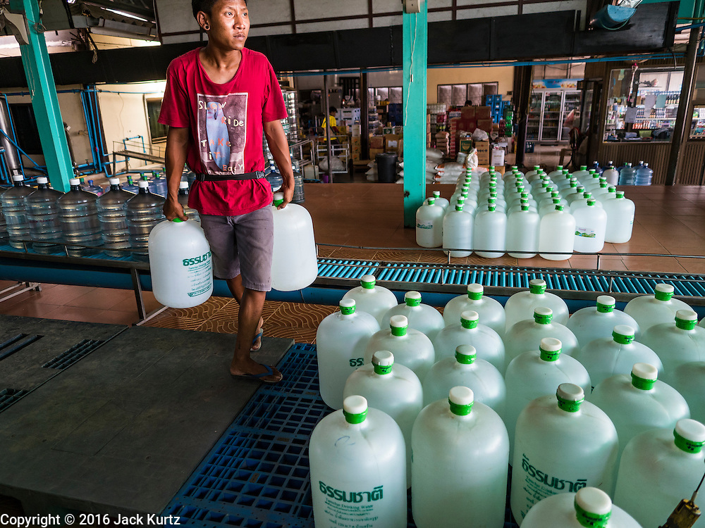 16 MARCH 2016 - BAN SONG, PRACHIN BURI, THAILAND:  A worker carries bottles of water out of a water bottling plant in Ban Song. The plant has been open for 11 years and is reporting that demand has increased above normal this year because more people are buying bottled water because salt water has intruded into the local water supply. Some people are buying the bottled water to wash and bathe with because of the salt water intrusion. The drought in Thailand is worsening and has spread to 14 provinces in the agricultural heartland of Thailand. Communities along the Bang Pakong River, which flows into the Gulf of Siam, have been especially hard hit since salt water has intruded into domestic water supplies as far upstream as Prachin Buri, about 100 miles from the mouth of the river at the Gulf of Siam. Water is being trucked to hospitals in the area because they can't use the salty water.   PHOTO BY JACK KURTZ
