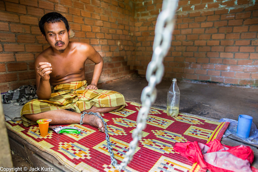 29 OCTOBER 2012 - MAYO, PATTANI, THAILAND: A resident eats in his room at the Bukit Kong home in Mayo, Pattani. He said he is a survivor of the Tak Bai incident in which the Thai army killed more than 80 people protesting against the government. He said he didn't remember his name or how he came to be at the home. The home opened 27 years ago as a ponoh school, or traditional Islamic school, in the Mayo district of Pattani. Shortly after it opened, people asked the headmaster to look after individuals with mental illness. The headmaster took them in and soon the school was a home for the mentally ill. Thailand has limited mental health facilities and most are in Bangkok, more than 1,100 kilometers (650 miles) away. The founder died suddenly in 2006 and now his widow, Nuriah Jeteh, struggles to keep the home open. Facilities are crude by western standards but the people who live here have nowhere else to go. Some were brought here by family, others dropped off by the military or police. The home relies on donations and gets no official government support, although soldiers occasionally drop off food. Now there are only six patients, three of whom are kept chained in their rooms.  Jeteh says she relies on traditional Muslim prayers, holy water and herbal medicines to treat the residents. Western style drugs are not available and they don't have a medic on staff.     PHOTO BY JACK KURTZ