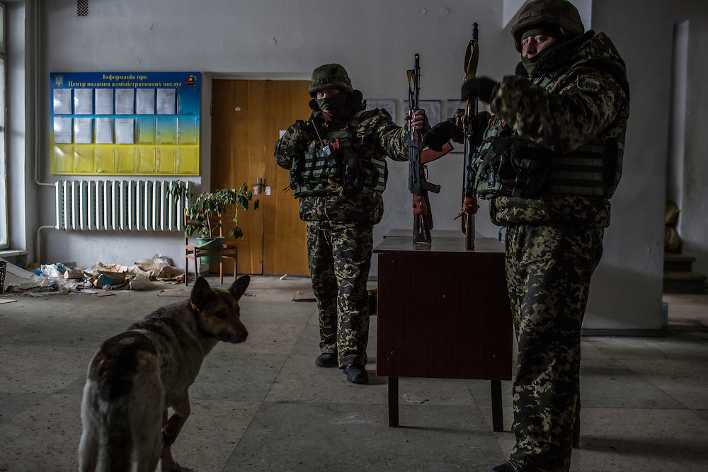 DEBALTSEVE, UKRAINE - FEBRUARY 7, 2015: Ukrainian soldiers stand in the lobby of a municipal building in Debaltseve, Ukraine. The Ukrainian-controlled town, surrounded on three sides by rebel forces, has been undergoing heavy shelling for more than a week, but a brief ceasefire allowed many residents to evacuate and others to simply venture out from their homes. CREDIT: Brendan Hoffman for The New York Times