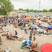 LÉGENDE: Aperçu du marché de Ngeuli en pleine journée. Les activités sont très intenses surtout dans la matinée. LIEU: Marché de Chagoua, N'Djaména, Tchad. PERSONNE(S): Vue plongée du marché de N'gueli. Vendeurs/vendeuses et clients. Un apperçu de la ville de N'Djaména (en arrière plan).