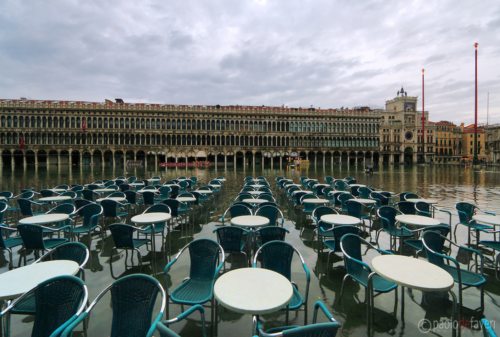 """The tables and chairs of Café Florian in Piazza San Marco floating in about 30 cms (1 foot) of water. Taken on an early morning at the end of January when the rising tide had already completely flooded the city, producing that phenomenon known as """"acqua alta""""."""