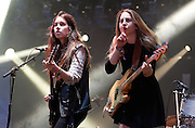 Danielle Haim and Este Haim of Haim perform live on the NME/Radio 1 stage during day three of Reading Festival at Richfield Avenue on August 25, 2013 in Reading, England.  (Photo by Simone Joyner)