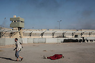 Libyan rebel walks by a dead loyalist during the assault on Bab Al Azizyia,  Gadhafi's headquarters in Tripoli. After a Caterpillar teared up a breach in the outer wall and rammed the main gate, the rebels stormed compound. 23 August 2011.