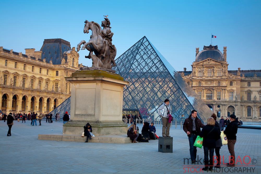 Louis XIV statue (Sun King) and Crystal Pyramid in front of the Louvre Museum.<br /> Paris, France.