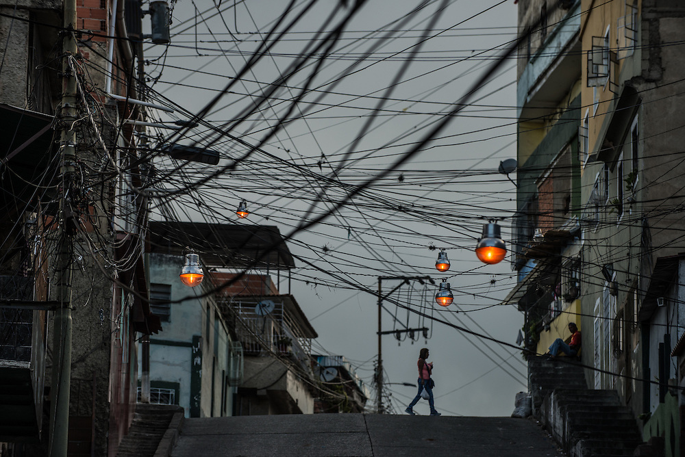CARACAS, VENEZUELA - MAY 20, 2016:  People walk under power lines in Catia, a slum in western Caracas. Despite having the largest known oil reserves in the world, the Venezuelan government is having difficulties providing basic services like electricity and running water. They are currently rationing both. Most emblematic has been perhaps one of the most desperate measures ever by a government to save electricity: A shut down of nearly all government buildings to all but two (part-time) days each week. Government employees in Venezuela only go to work now on Mondays and Tuesdays.  All public schools now have a three-day weekend, taking off Fridays in order to save electricity.  PHOTO: Meridith Kohut