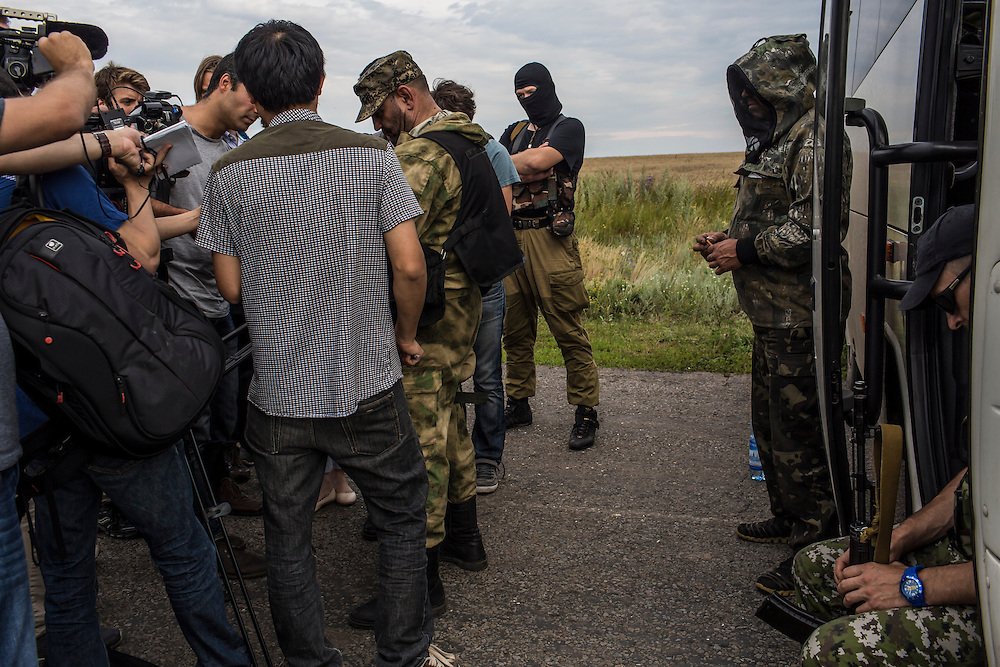 GRABOVO, UKRAINE - JULY 19: A separatist fighter speaks to reporters at the scene of the crash of Malaysia Airlines flight MH 17 after establishing control of the site on July 19, 2014 in Grabovo, Ukraine. Malaysia Airlines flight MH17 was travelling from Amsterdam to Kuala Lumpur when it crashed killing all 298 on board including 80 children. The aircraft was allegedly shot down by a missile and investigations continue over the perpetrators of the attack. (Photo by Brendan Hoffman/Getty Images) *** Local Caption ***