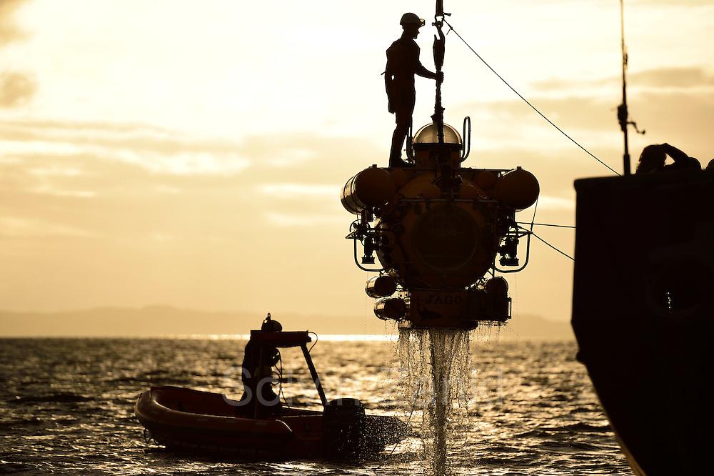 """Das Forschungstauchboot JAGO wird im Trondheimfjord aus dem Wasser an Bord der FS Poseidon gehoben. Zum Befestigen des Hakens ist ein Helfer im Taucheranzug mit """"an Bord"""" des Tauchbootes Trondheimfjord Norwegen"""