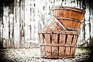 Three empty apple orchard baskets stacked in front of the barn