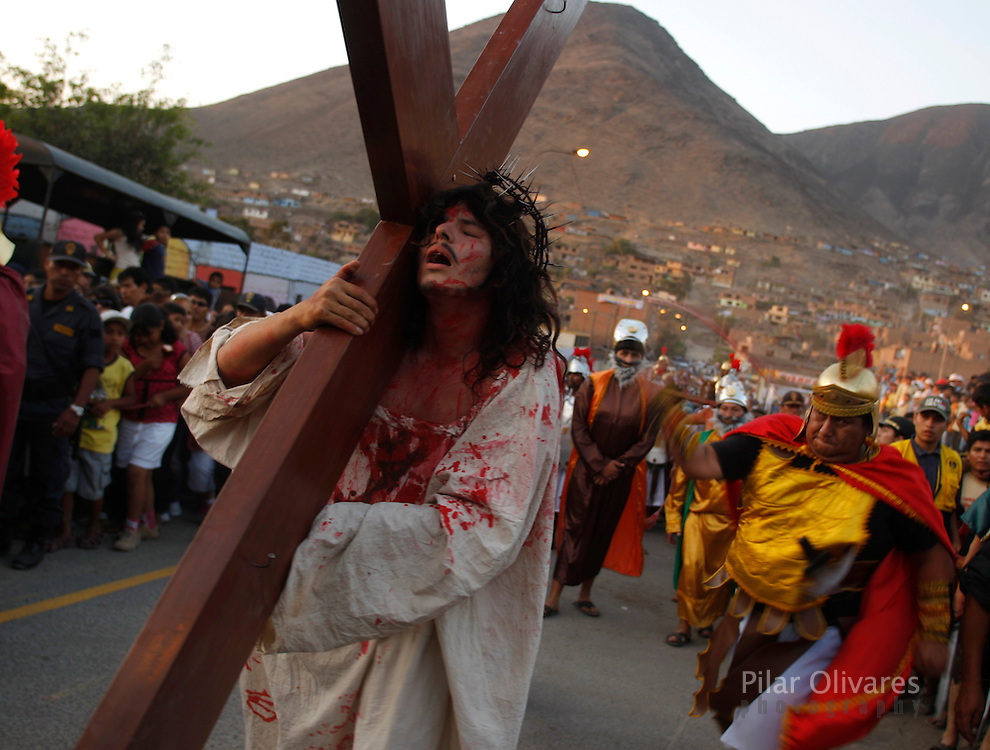 """An actor playing the role of Jesus Christ carries a cross as he is """"whipped"""" in the re-enactment of the crucifixion of Jesus Christ on Good Friday during Holy Week on the outskirts of Lima April 2, 2010."""