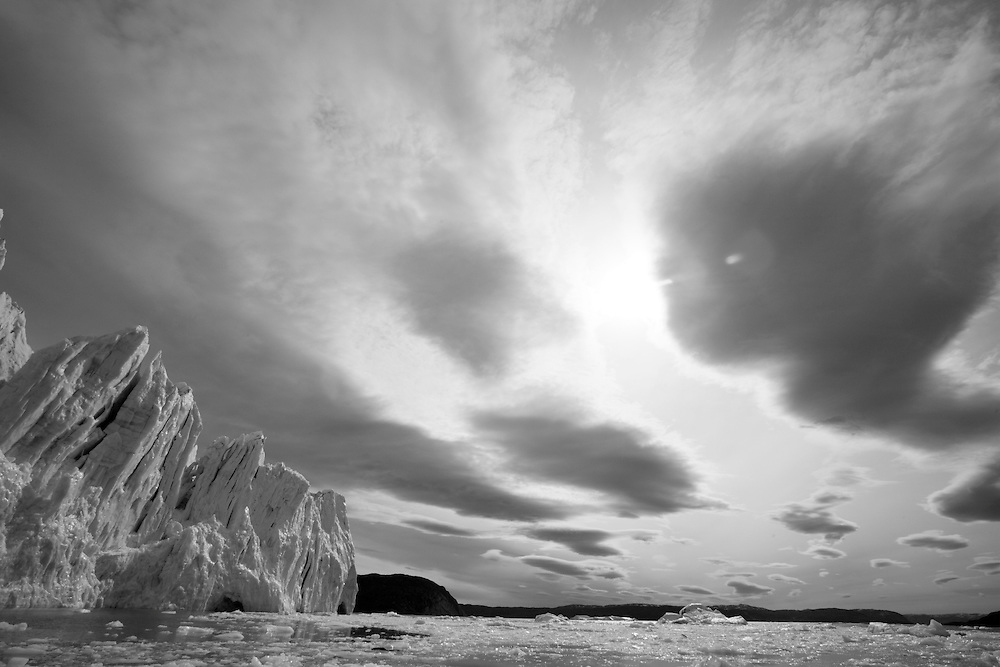 Greenland, Disko Bay, Black and white image of icebergs floating near active face of Kangilerngata Sermia Glacier on summer morning